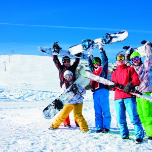 Five positive friends standing and holding snowboards and skies together on the beautiful mountain background
