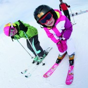 Young girl learning how to ski with family