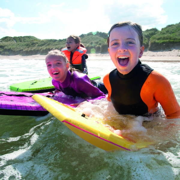Three girls are smiling for the camera as they bodyboard in the