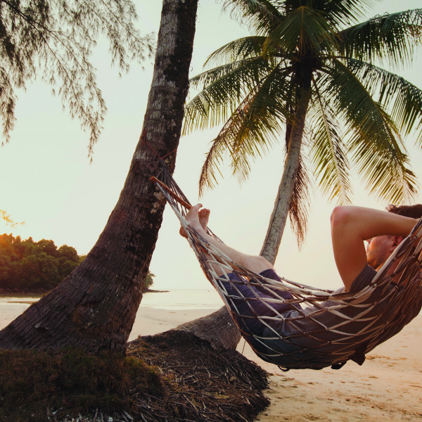 tourist relaxing in hammock on tropical beach with coconut palm
