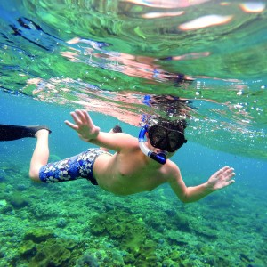 Underwater shoot of a young boy snorkeling and diving in a tropical sea in Nusa penida, Indonesia, Bali