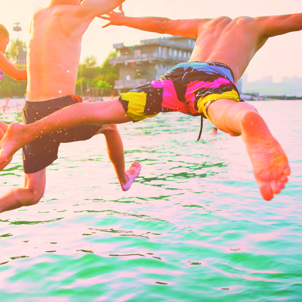 Group of happy crazy people having fun jumping in the sea water from boat. Friends jump in mid air on sunny day summer pool party at diving holiday. Travel vacation, friendship, youth holiday concept.