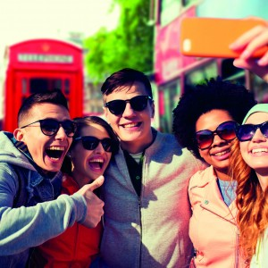 people, leisure, friendship and technology concept - group of smiling teenage friends taking selfie with smartphone over london city street background