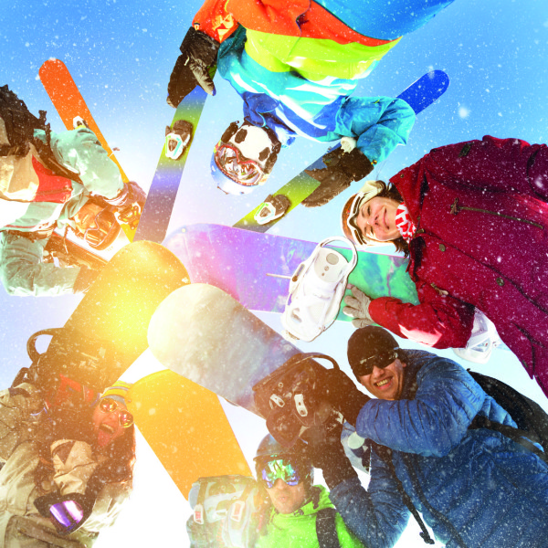Group happy snowboarders skiers circle
