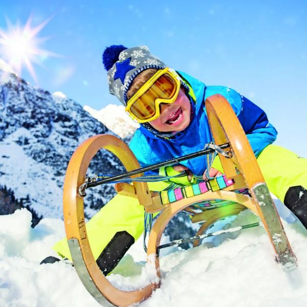 Junge in den Alpen mit Schlitten