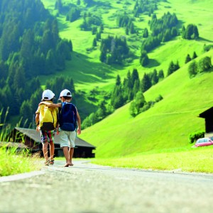 Two little children, boy brothers with backpacks travel on the road to scenic mountains, summertime