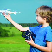 Boy playing with drone outdoors.